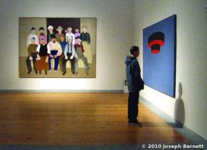 Man viewing painting by Joseph Barnett.